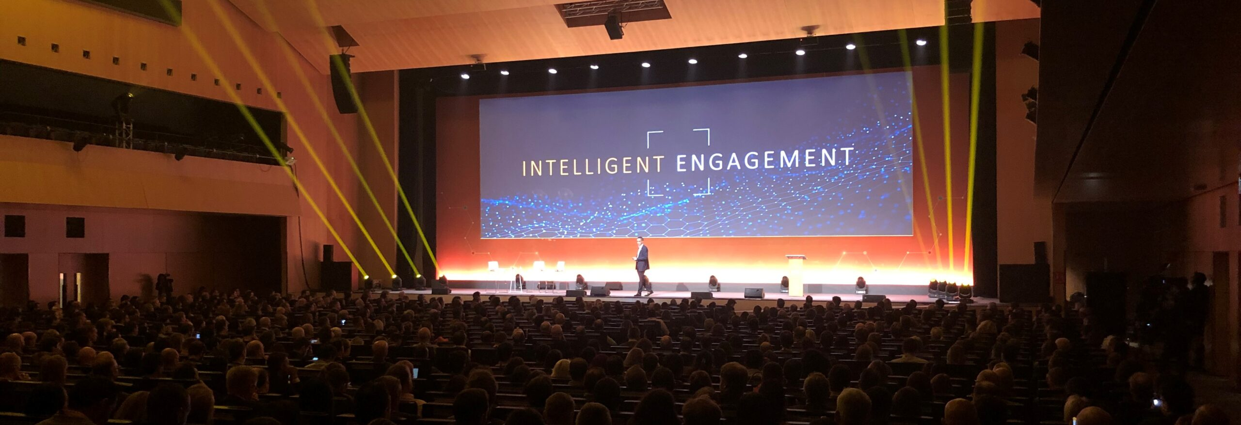 Image of a stage at an event with the words intelligent enablement on the screen